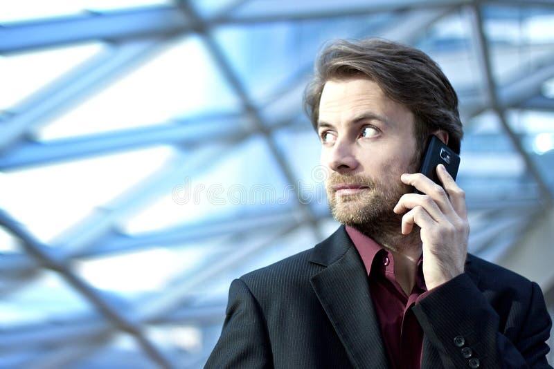 Ringer inre kontorsbyggnad för affärsmannen som talar på en mobil royaltyfri bild