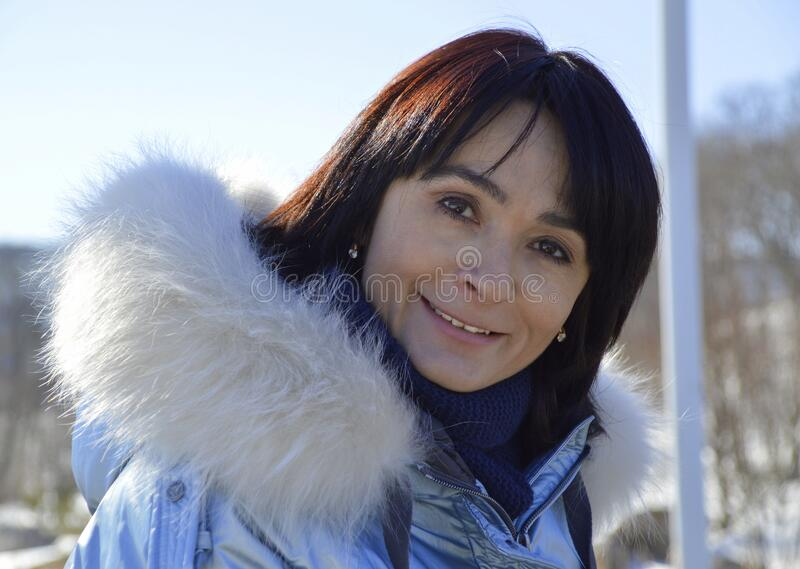 Forty five year old Russian woman sincerely, naturally and kindly smiling, looking at the camera on an early spring  day.  stock photos