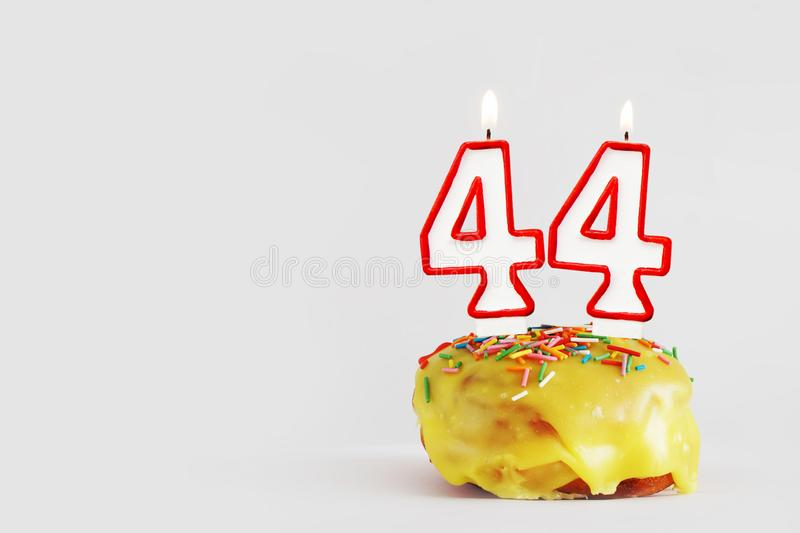 Forty four years anniversary. Birthday cupcake with white burning candles with red border in the form of number Forty four royalty free stock photo