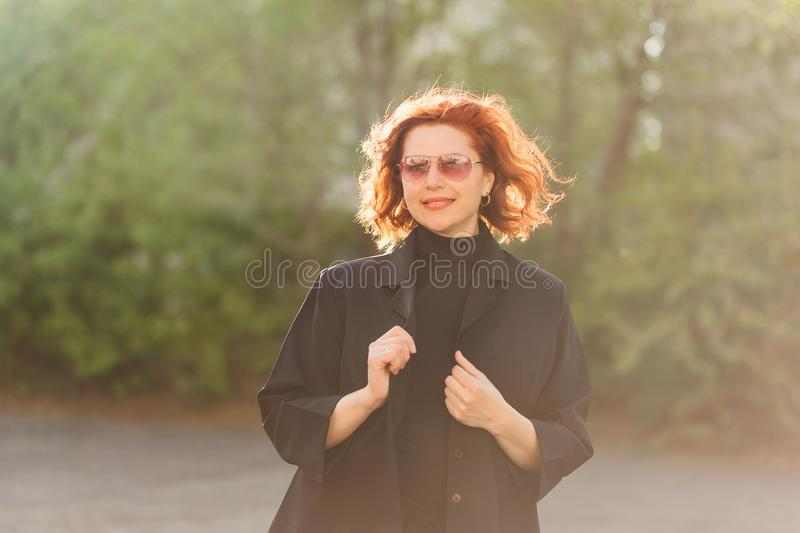 Forty-year-old red-haired smiling woman in sunglasses on a soft blurred background outdoors. Woman in soft contoured sunlight stock images