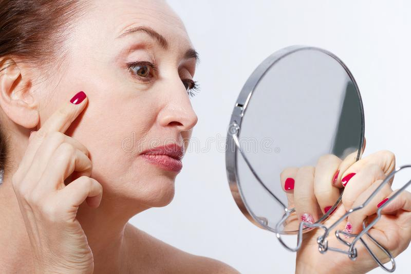 Forty years old woman looking at wrinkles in mirror. Plastic surgery and collagen injections. Makeup. Macro face. Selective face royalty free stock photography