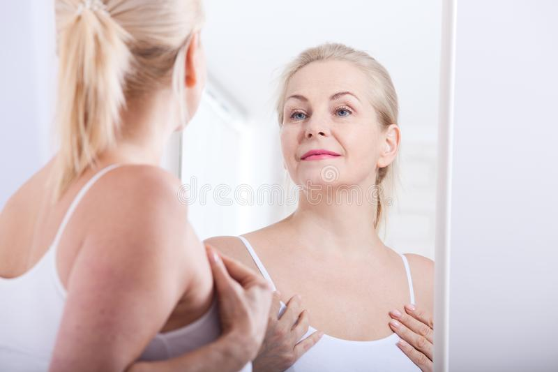 Forty years old woman looking at wrinkles in mirror. Plastic surgery and collagen injections. Makeup. Macro face. Selective focus stock photography