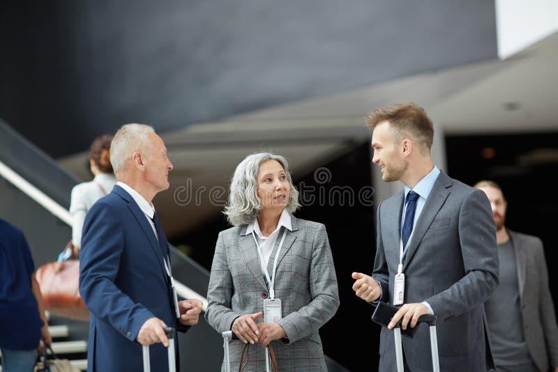 Forumdeltagare med resväskor royaltyfria bilder
