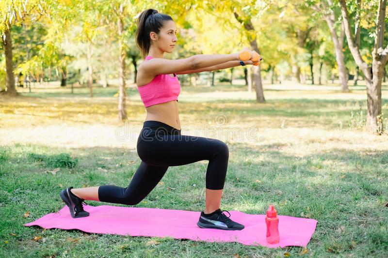 Forward lunges with weights on a pink mat royalty free stock image
