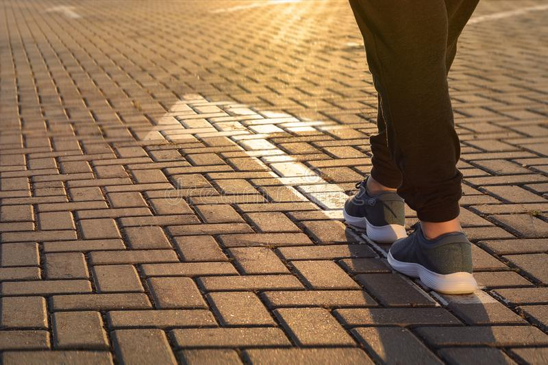 Forward moving. Feet on road arrow in the rays of setting sun stock photography