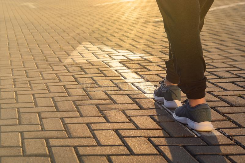 Forward moving. Feet on road arrow in the rays of setting sun royalty free stock photography
