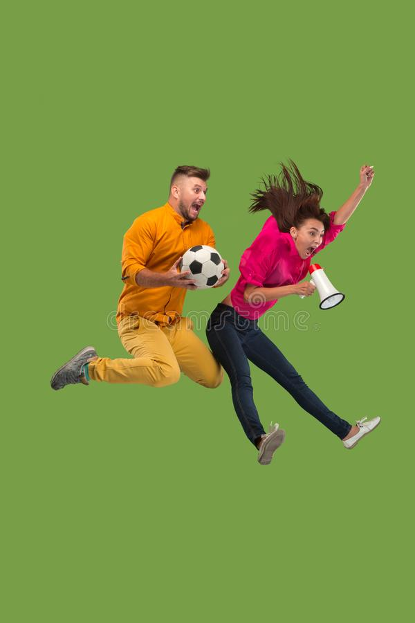 Forward to the victory.The young couple as soccer football player jumping and kicking the ball at studio on a green stock image