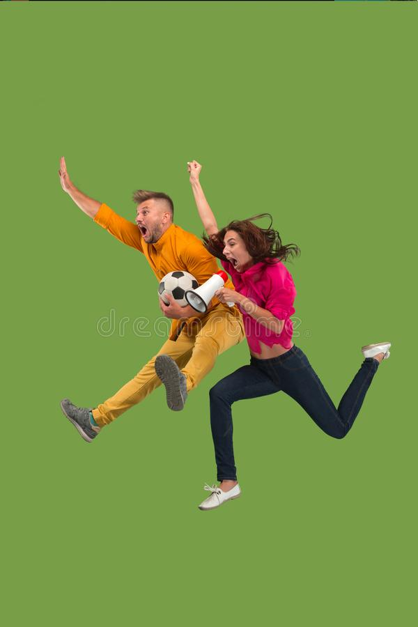 Forward to the victory.The young couple as soccer football player jumping and kicking the ball at studio on a green royalty free stock image