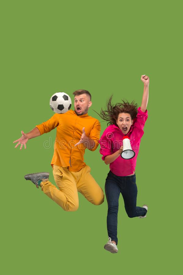 Forward to the victory.The young couple as soccer football player jumping and kicking the ball at studio on a green stock images
