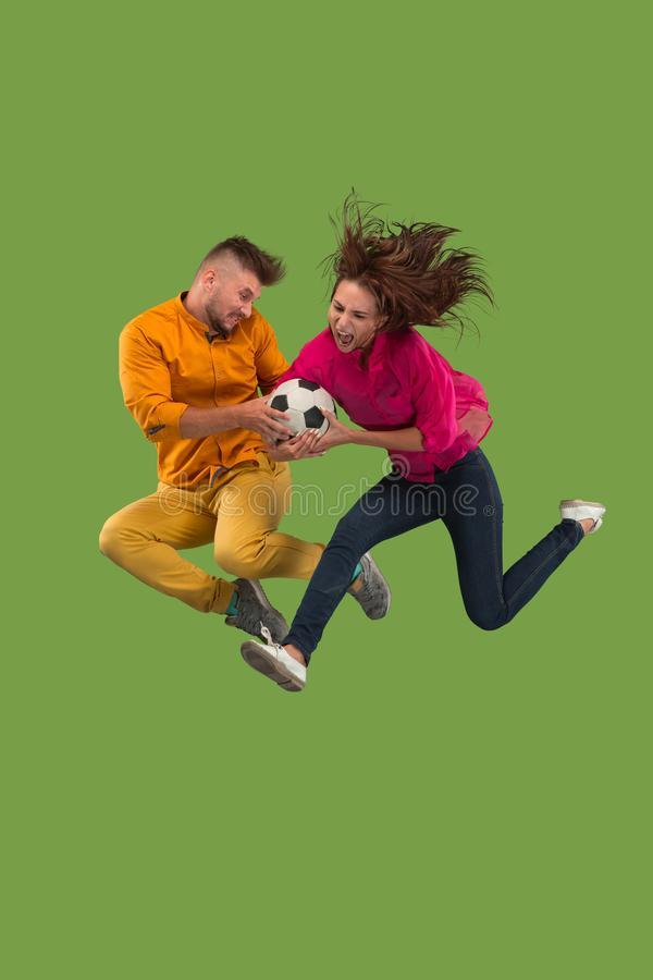 Forward to the victory.The young couple as soccer football player jumping and kicking the ball at studio on a green stock photos
