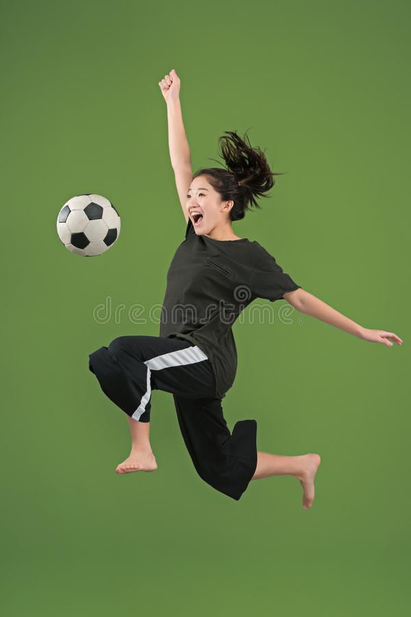 Forward to the victory.The young woman as soccer football player jumping and kicking the ball at studio on green royalty free stock photo