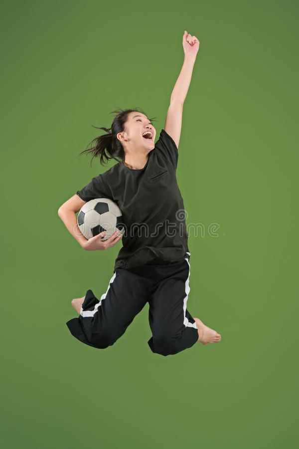 Forward to the victory.The young woman as soccer football player jumping and kicking the ball at studio on green stock photography