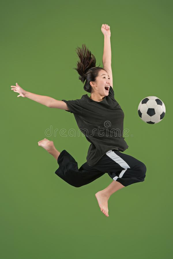 Forward to the victory.The young woman as soccer football player jumping and kicking the ball at studio on green stock photo