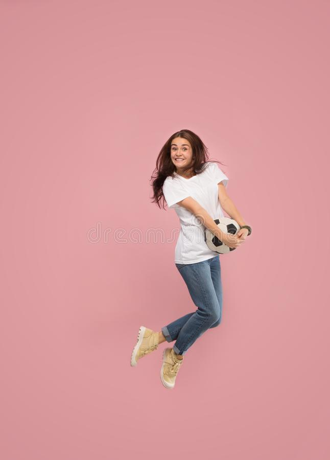 Forward to the victory.The young woman as soccer football player jumping and kicking the ball at studio on pink stock photos