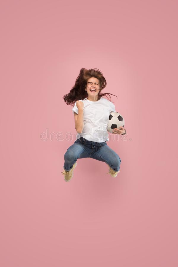 Forward to the victory.The young woman as soccer football player jumping and kicking the ball at studio on pink royalty free stock images