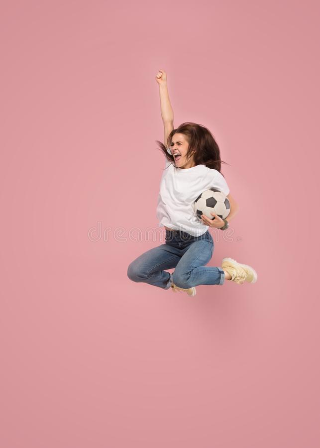 Forward to the victory.The young woman as soccer football player jumping and kicking the ball at studio on pink stock photography