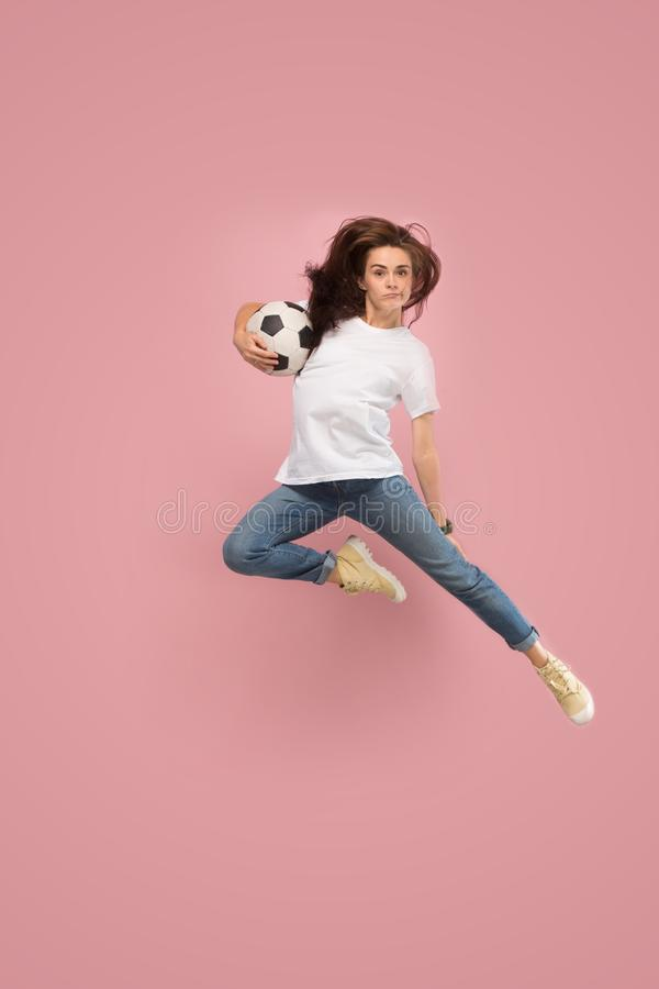 Forward to the victory.The young woman as soccer football player jumping and kicking the ball at studio on pink royalty free stock image