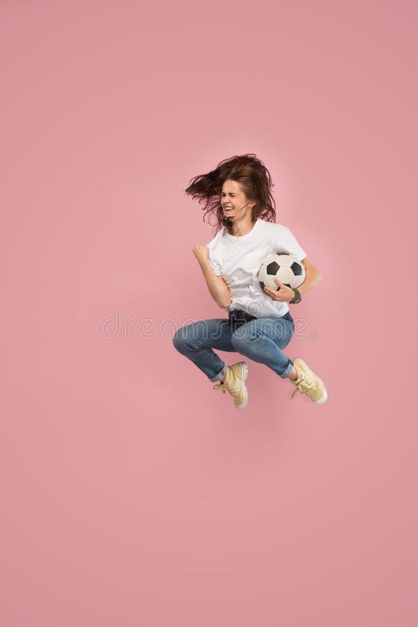 Forward to the victory.The young woman as soccer football player jumping and kicking the ball at studio on pink stock image