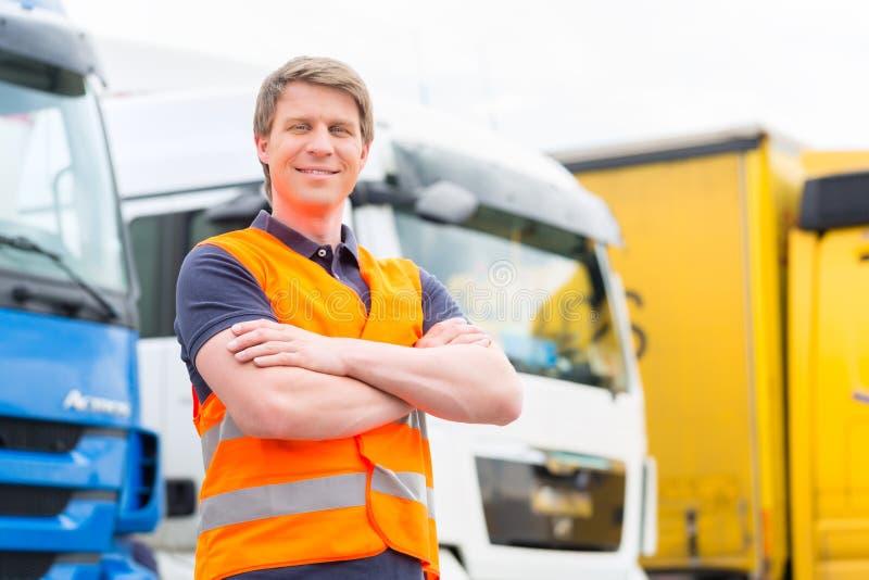 Forwarder eller chaufför framme av lastbilar i bussgarage arkivbild