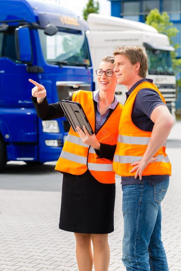 Forwarder framme av lastbilar på en bussgarage arkivbild
