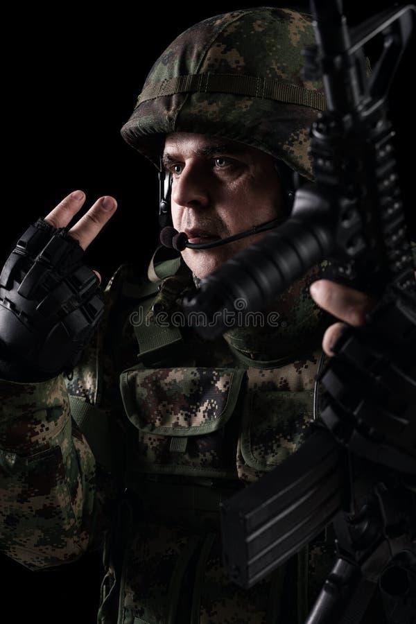 Forze speciali del soldato con il fucile su fondo scuro immagine stock