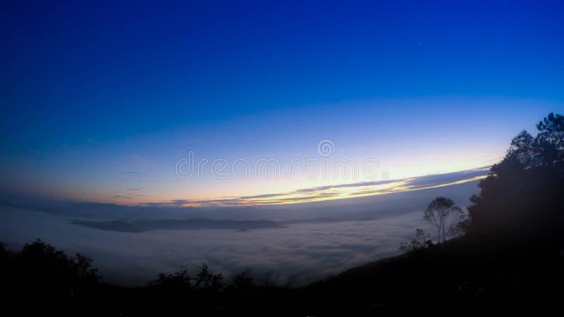 Foschia blu superiore di bella vista della nuvola della natura della montagna di paesaggio di alba del fondo della foresta della  immagine stock