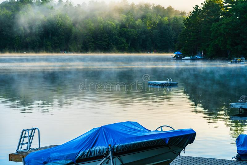 Foschia di primo mattino che solleva dal lago come le albe sopra a immagini stock
