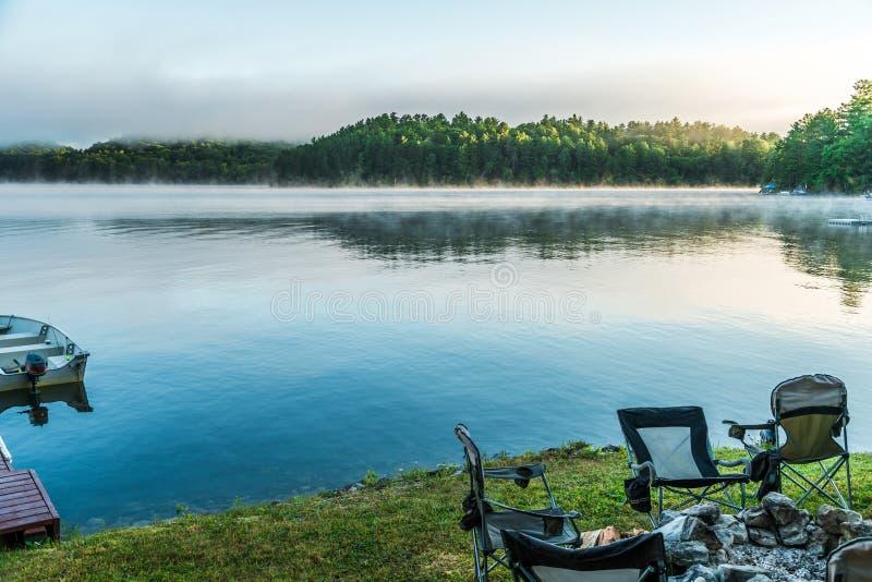 Foschia di primo mattino che solleva dal lago come le albe sopra a fotografia stock libera da diritti