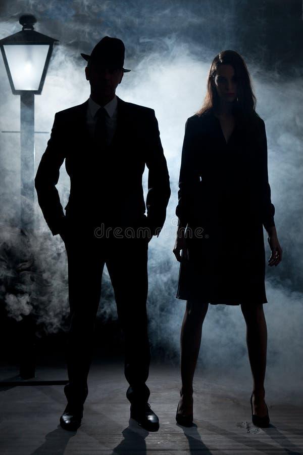 Foschia noir dell'iluminazione pubblica delle coppie del gangster del film fotografie stock