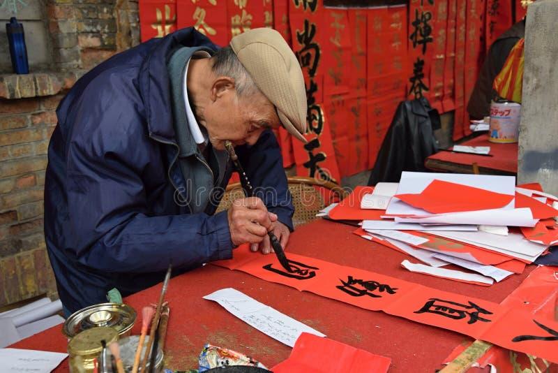 FOSHAN, CHINE - VERS EN JANVIER 2018 : Une écriture de vieil homme bénissant les couples antithétiques pendant le festival de pri photo libre de droits