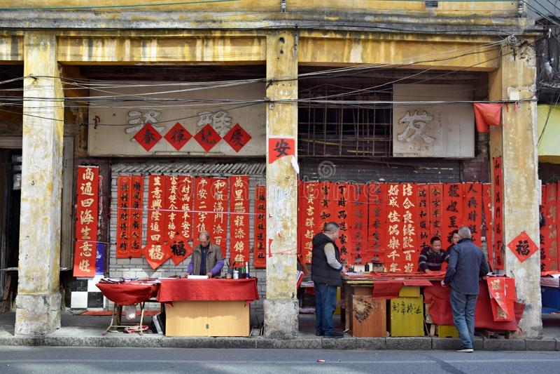FOSHAN, CINA - CIRCA GENNAIO 2019: I calligrafi sulla via stanno scrivendo i distici cinesi del nuovo anno o i distici della prim fotografie stock libere da diritti
