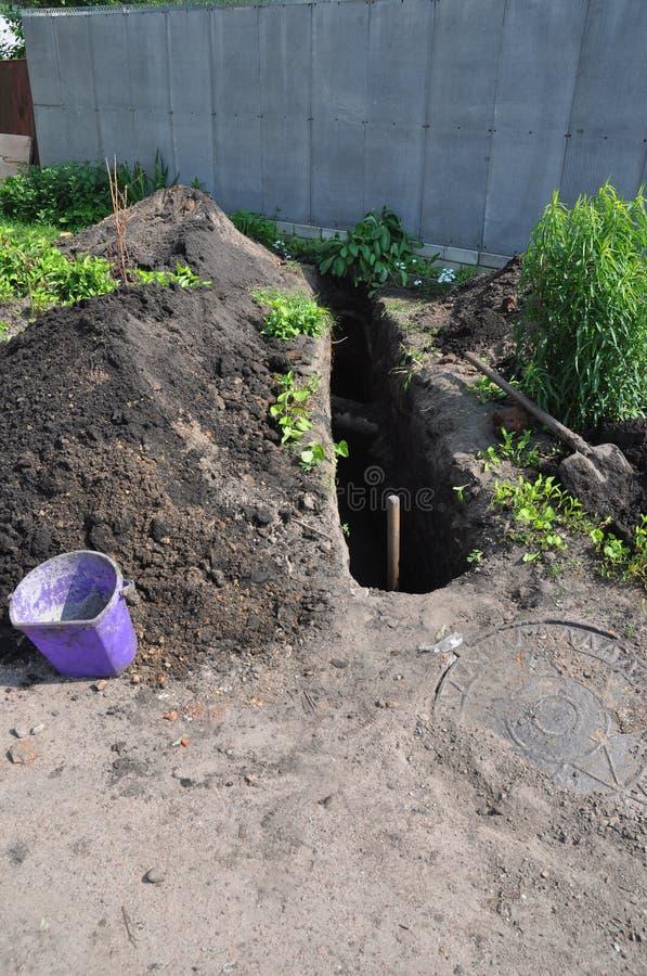 Fossa di scavatura per i tubi per fognatura durante la costruzione della casa Fossa per il tubo per fognatura sanitario nella cos fotografia stock