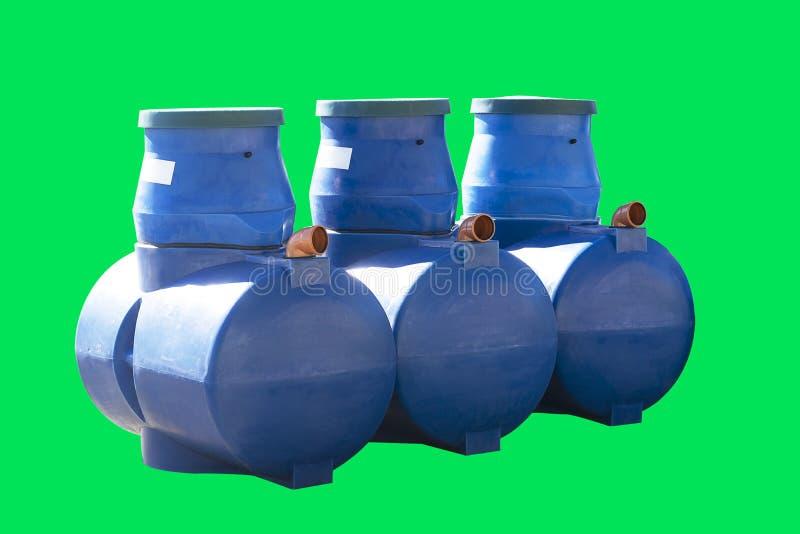Fossas sépticas plásticas azuis isoladas em um fundo verde Tambores para a água de esgoto foto de stock royalty free
