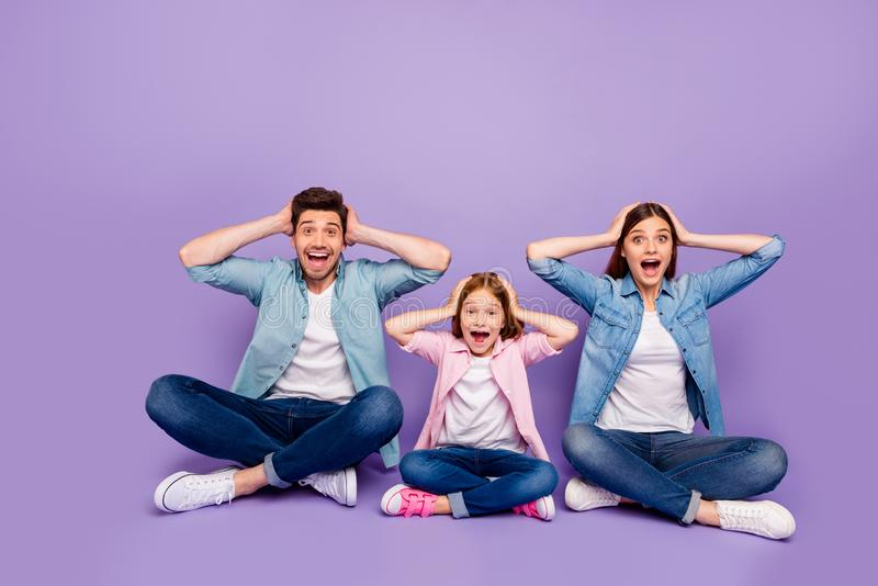 Foster family of three members sit floor holding head won lottery wear casual clothes  purple background royalty free stock photos