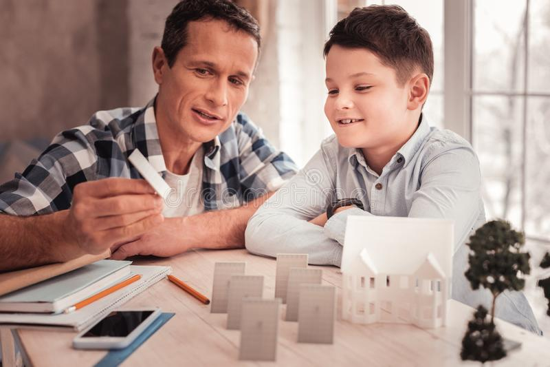 Foster father and his cute son building model of smart city. Smart city. Caring responsible foster father and his cute curious son building model of smart city royalty free stock image