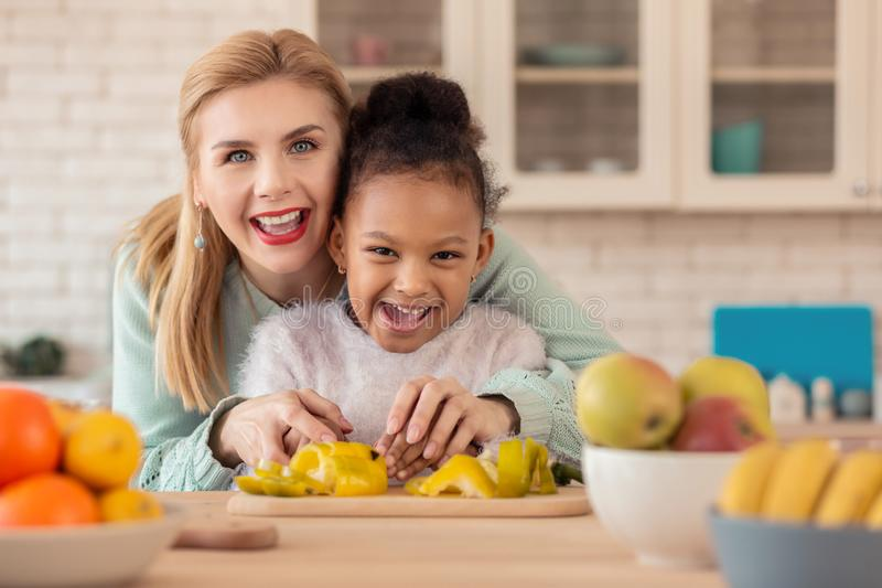 Foster mother feeling happy cooking together with her girl royalty free stock photography