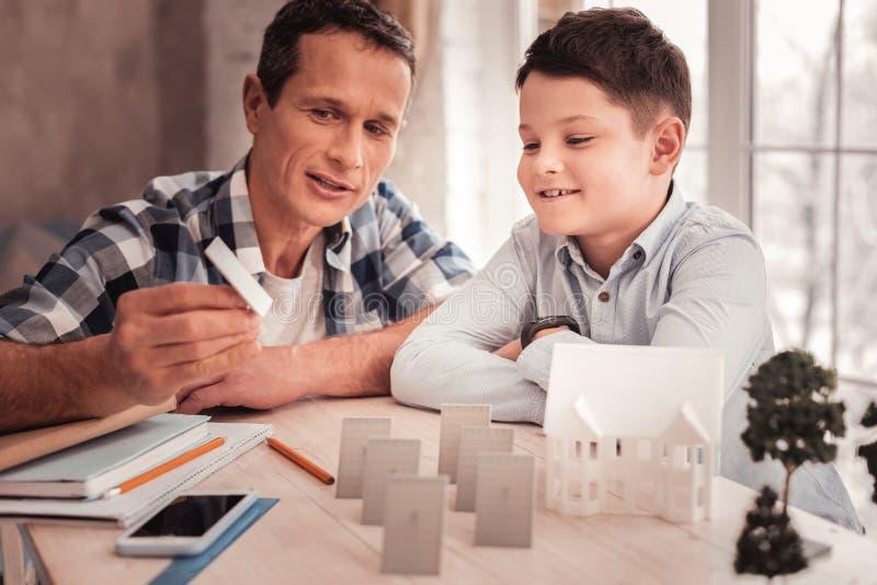 Fosterfar och hans gulliga sonbyggnadsmodell av den smarta staden arkivfoton