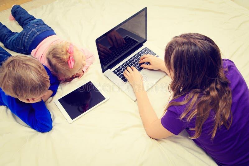 Fostra arbete på bärbara datorn medan ungar som ser arkivfoton