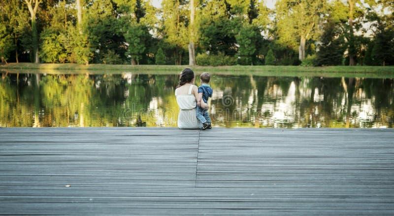 Fostra att bära hennes barn och att se sjön royaltyfri bild