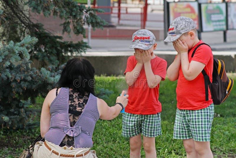 Fostra att bespruta krypimpregneringsmedel på barn med sprejflaskan i Volgograd royaltyfria bilder