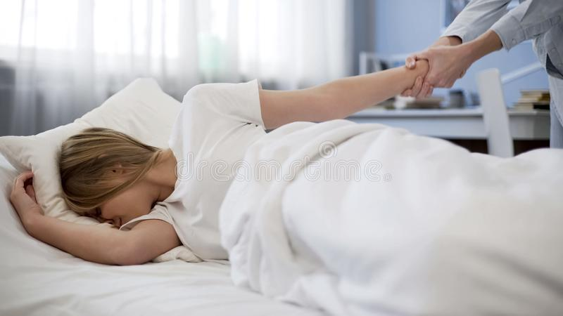 Fostra att dra dotterhanden som försöker att vakna upp henne, sent till skolan, problemungen royaltyfria foton