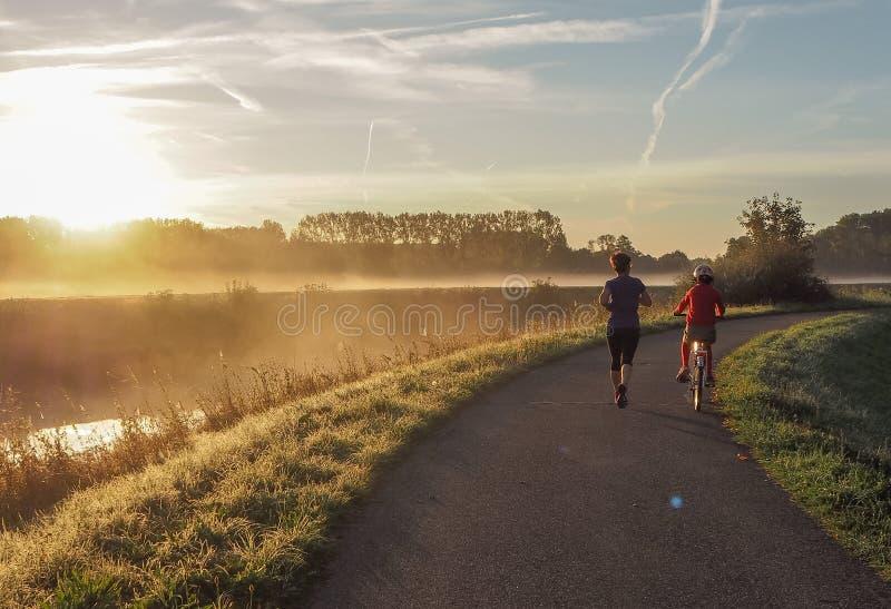Fostra att gå för en körning, medan medföljt av hennes son på en cykel royaltyfria bilder