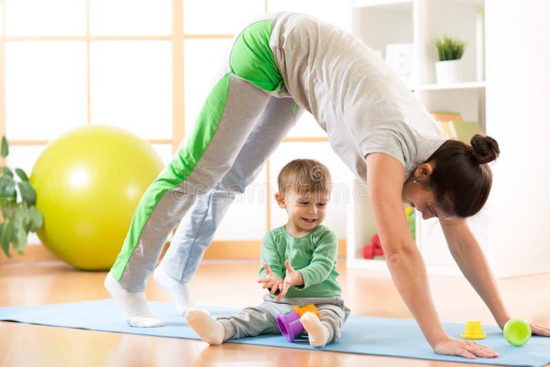 Fostra att göra yoga, eller konditionövningar med behandla som ett barn royaltyfri foto