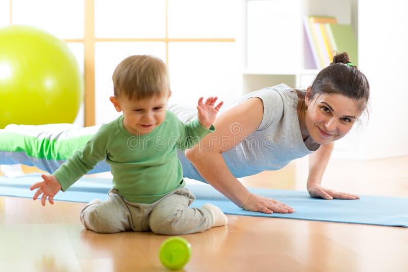Fostra att göra yoga, eller konditionövningar med behandla som ett barn royaltyfri bild