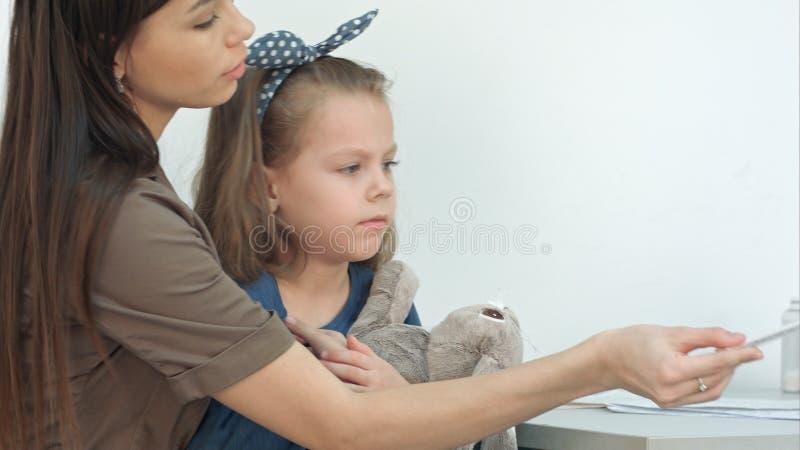 Fostra att ge termometern tillbaka för att manipulera medan hennes dotter som spelar med kaninen arkivbilder