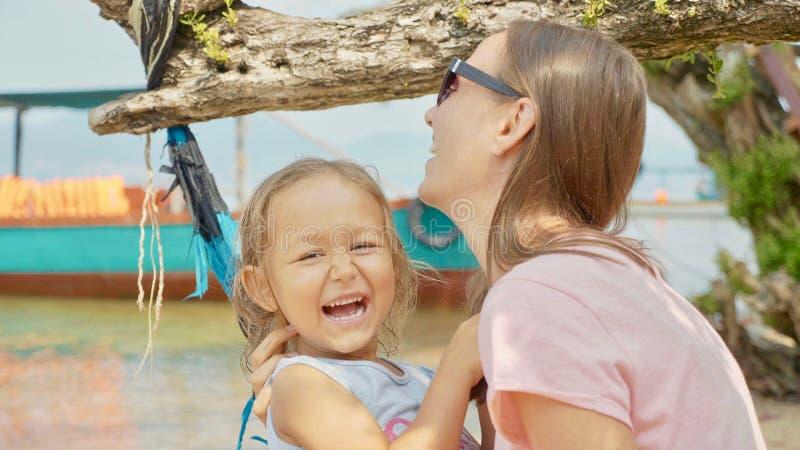 Fostra att ha gyckel med hennes lilla gulliga dotter på hängmattan på den sandiga stranden arkivbild