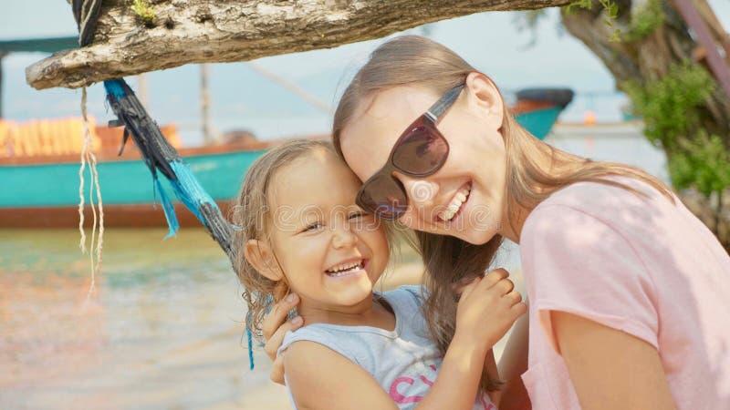 Fostra att ha gyckel med hennes lilla gulliga dotter på hängmattan på den sandiga stranden royaltyfria foton