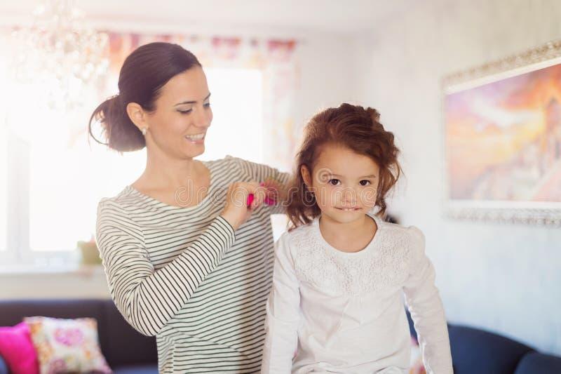 Fostra att kamma hår av hennes dotter i morgonen fotografering för bildbyråer
