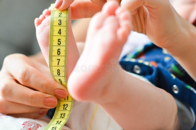 Fostra att mäta som är mycket litet, behandla som ett barn foten med en meter fotografering för bildbyråer