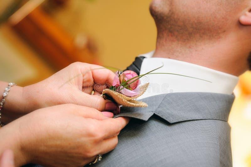 Fostra att sätta en blomma i knapphålet av brudgumklänningen arkivfoto